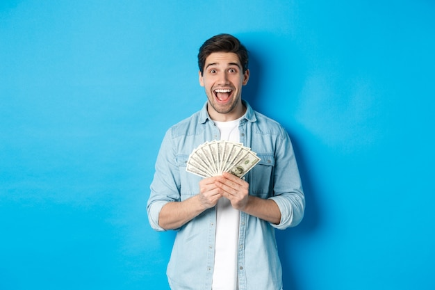 Opgewonden en verraste aantrekkelijke man, die geldprijs vasthoudt en verbaasd glimlacht, staande over blauwe achtergrond