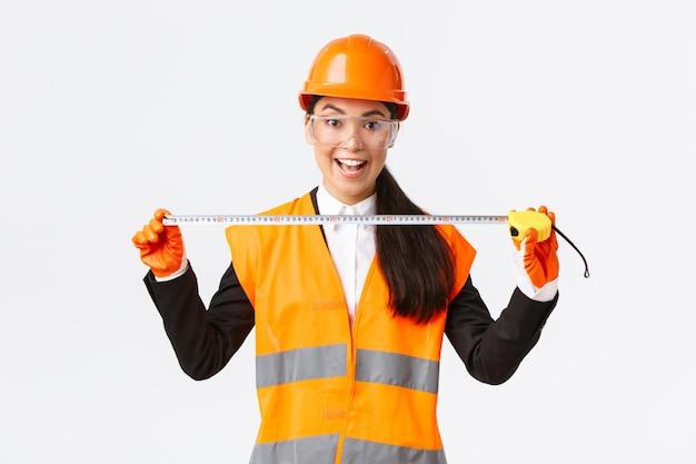 Opgewonden en vrolijke aziatische vrouwelijke bouwingenieur die lay-out meet, meetlint vasthoudt en glimlacht, klaar voor werk om iets te bouwen, staande op een witte achtergrond in veiligheidshelm