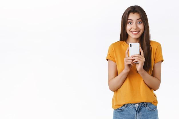 Opgewonden, enthousiaste knappe brunette vrouw woont een geweldig evenement bij, houdt een smartphone in de buurt van de borst, glimlacht verbaasd en geamuseerd recordvideo van concert of coole uitvoering