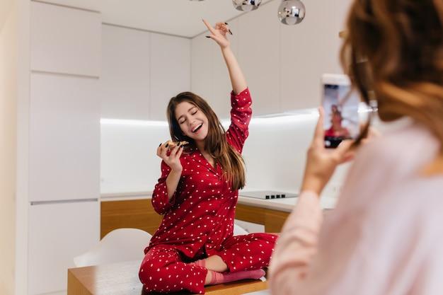 Opgewonden europees meisje dat pizza eet tijdens huisfotoshoot. schattige vrouw in rode nachtkleding zittend op tafel terwijl haar zus fotograferen met telefoon.