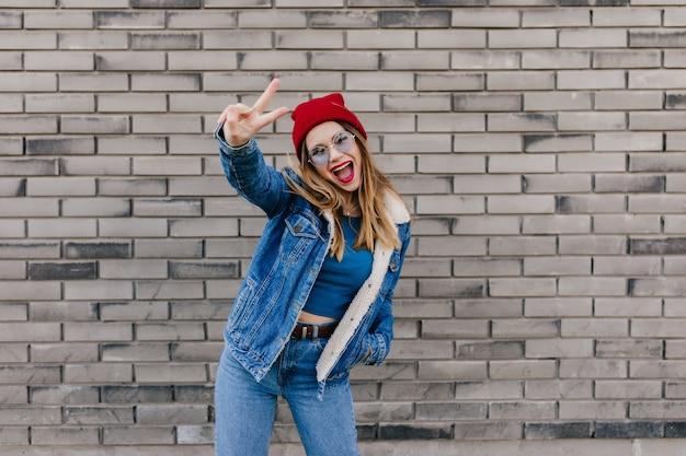 Opgewonden europese vrouw met blij gezicht expressie dansen op bakstenen muur. buiten schot van positieve stijlvolle meisje in rode hoed gek rond op straat.