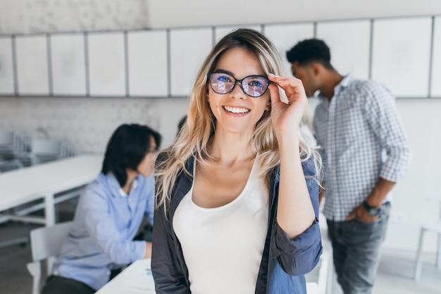 Opgewonden europese vrouwelijke student met bril en poseren tussen lezingen. indoor portret van lachende vrouw naast aziatische en afrikaanse universiteitsgenoten tijdens seminar.