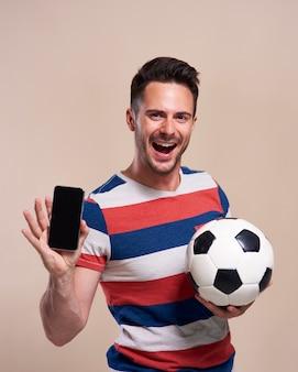 Opgewonden fan die voetbal vasthoudt en mobiele telefoon laat zien