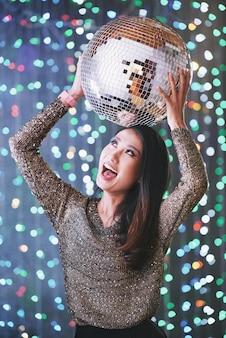 Opgewonden feestende jonge vrouw met discobal