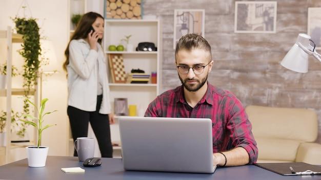 Opgewonden freelancer na het lezen van een goed nieuws op laptop tijdens het werken in de woonkamer.