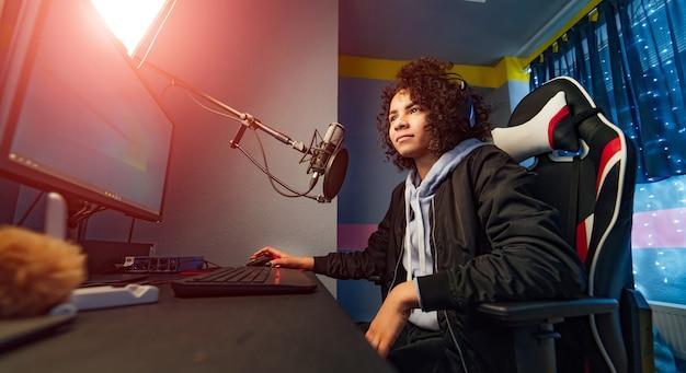 Opgewonden gamermeisje in hoofdtelefoon met een microfoon die online videogame speelt op een personal computer. praten met andere spelers. kamer en pc hebben kleurrijke warme neon led-verlichting. gezellige avond thuis.