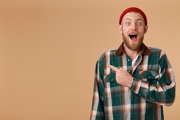 Opgewonden gelukkig bebaarde emotionele man in rode hoed heeft gezichtsuitdrukking verrast, wijst met wijsvinger in de linkerhoek
