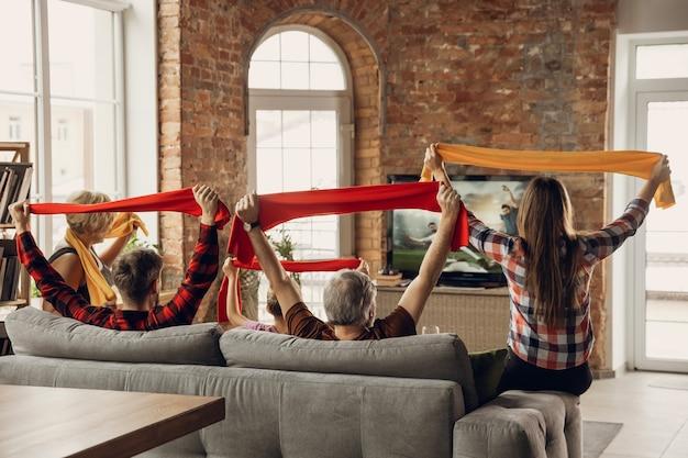 Opgewonden, gelukkig groot familieteam kijken samen naar sportwedstrijden op de bank thuis
