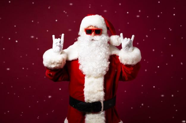 Opgewonden gelukkig hipster kerstman in hoofdtelefoons en zonnebril heeft plezier op het feest