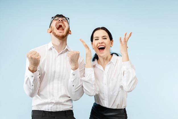 Opgewonden gelukkig jong koppel met verrukking. zakenman en vrouw geïsoleerd op blauwe muur