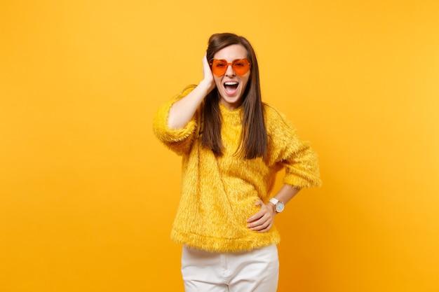 Opgewonden gelukkig jong meisje in bonttrui, witte broek en hartoranje bril die hand in de buurt van hoofd houdt geïsoleerd op felgele achtergrond. mensen oprechte emoties, lifestyle concept. reclame gebied.