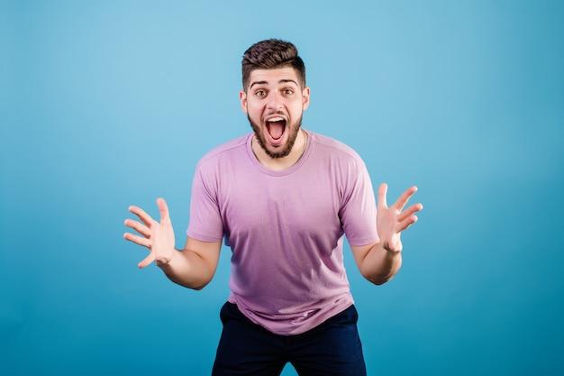 Opgewonden gelukkig jonge man handen schudden geïsoleerd op blauw