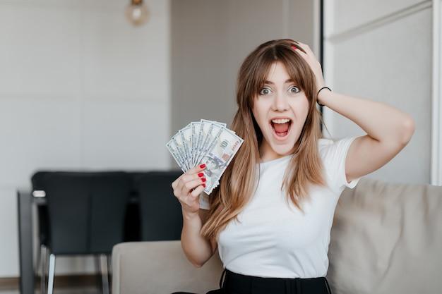 Opgewonden gelukkig jonge vrouw met geld dollar biljetten in de hand schreeuwen zittend op een bank thuis