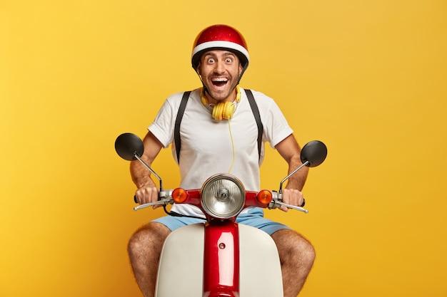 Opgewonden gelukkig knappe mannelijke chauffeur op scooter met rode helm