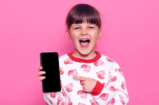 Opgewonden gelukkig lachend vrouwelijk soort met geopende mond mobiele telefoon in handen houden en wijzend op blanco display met wijsvinger, poseren geïsoleerd over roze muur.