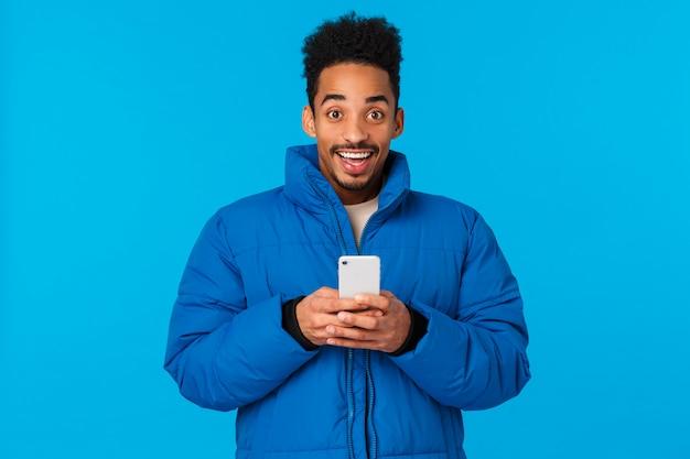 Opgewonden gelukkig lachende afrikaanse amerikaan in gewatteerd winterjasje, smartphone vasthoudend en grijnzend vrolijk, ontvang uitnodigingsfeest, kletsende vrienden, werd beroemd op sociale media, blauw