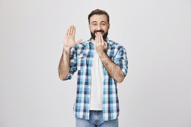 Opgewonden gelukkig lachende man hallo zegt, hand in groet zwaaien