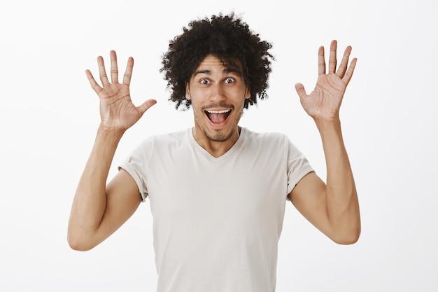 Opgewonden gelukkig man die grote aankondiging maakt, handen opsteken van vreugde