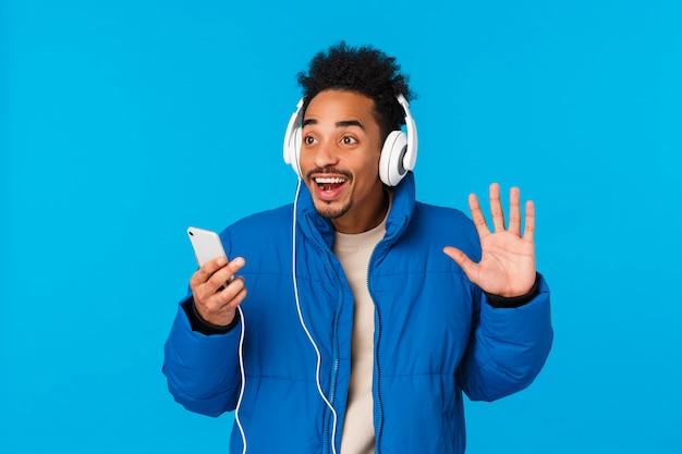 Opgewonden gelukkig man luistert naar kerstliedjes als vriend op straat, hallo zeggend, vriendelijk zwaaiende linkerhand hallo gebaar, koptelefoon dragen, genieten van muziek, smartphone vasthouden, blauwe achtergrond glimlachen
