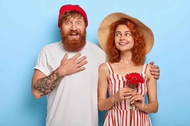 Opgewonden gelukkig man raakt borst, onder de indruk van goed nieuws, omhelst vriendin die rode gerbera vasthoudt, lopen samen