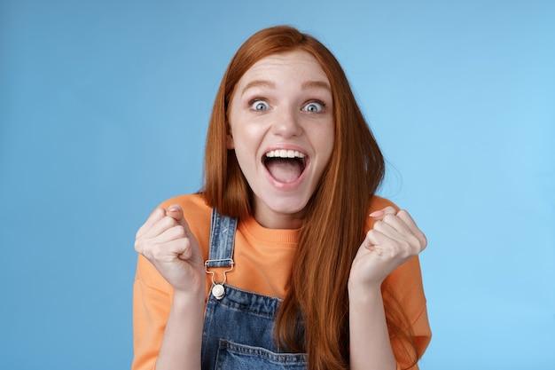 Opgewonden gelukkig overweldigd schattig roodharig meisje blauwe ogen hardop schreeuwen verheugend fantastisch geweldig nieuws gebalde vuisten triomferen vieren overwinning winnen staand verbaasd blauwe achtergrond succes behalen