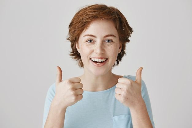 Opgewonden gelukkig roodharige meisje poseren tegen de witte muur