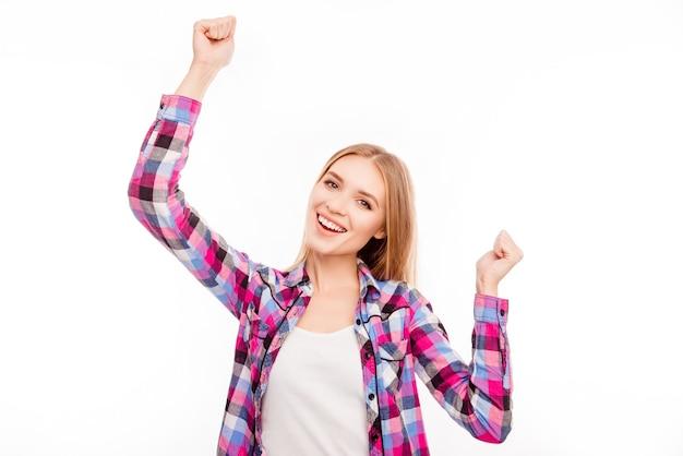 Opgewonden gelukkig succesvolle vrouw zegevierend met opgeheven handen