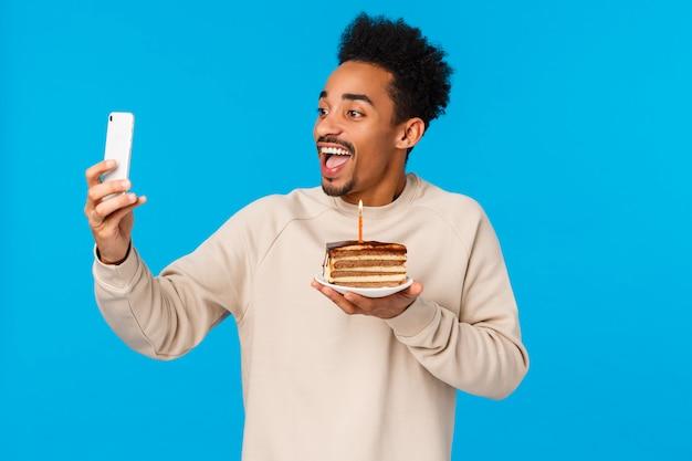 Opgewonden gelukkige afro-amerikaanse bebaarde hipster man met stuk taart met verjaardagskaars, vrolijk glimlachend selfie maken of video opnemen hoe hij viert, wens doet, staande blauwe muur
