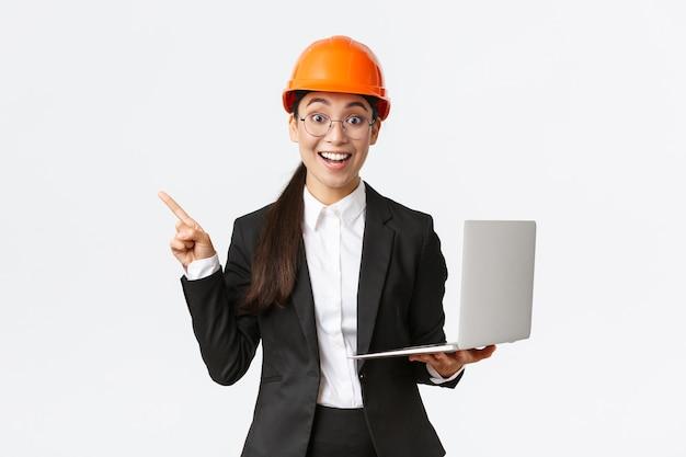 Opgewonden gelukkige aziatische vrouwelijke ingenieur, industriële vrouw in veiligheidshelm en pak, presentatie tonen, vinger wijzen naar grafiek of grafiek en laptopcomputer vasthouden, verbaasd glimlachend