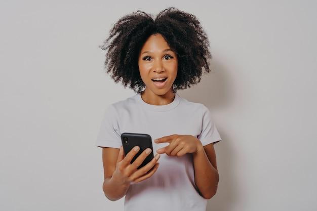 Opgewonden gelukkige donkere dame met krullend haar die mobiele telefoon vasthoudt en goed nieuwsmelding leest, geniet van chatten met vrienden of online winkelen, geïsoleerd op een witte studioachtergrond