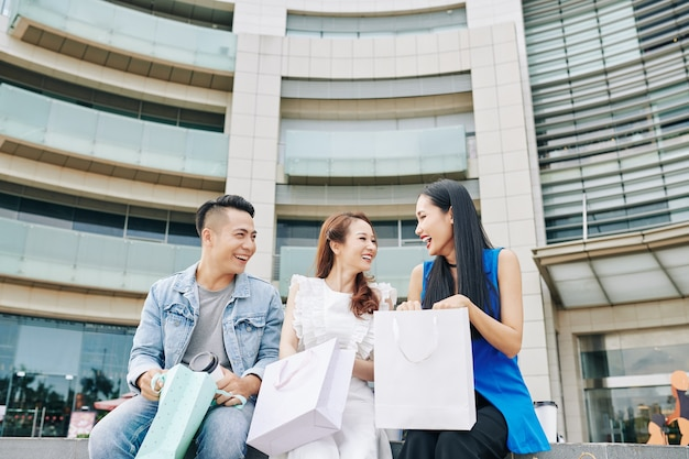 Opgewonden gelukkige jonge aziatische mensen zitten buiten het winkelcentrum na het winkelen in de uitverkoop