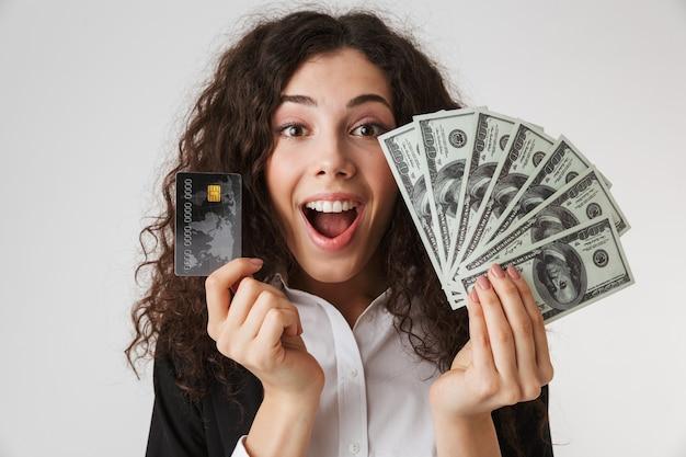 Opgewonden gelukkige jonge bedrijfsvrouw met creditcard en geld.