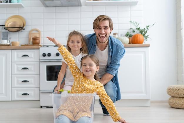 Opgewonden gelukkige jonge vader rennen kartonnen doos met kleine schattige kinderen, dochters rijden naar binnen, plezier maken.