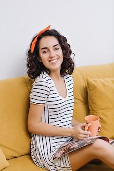 Opgewonden gelukkige jonge vrouw rusten op de bank, tijdschrift lezen, met vrije tijd in modern appartement. vrolijke bui, thee drinken, genieten, relaxen, comfort in huis