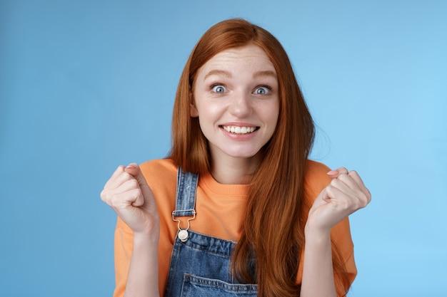 Opgewonden gelukkige jonge vrouwelijke collega krijgt uitstekende gelegenheid triomfantelijke blij lachende camera gebalde vuisten vieren overwinning succes verheugd fantastisch goed nieuws verrast. ruimte kopiëren