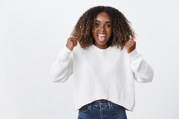 Opgewonden gelukkige knappe vrouwelijke afro-amerikaanse vrouw krullend afro kapsel juichen gelukkig schreeuwen ja volbracht doel, droom die uitkomt, succes behaald, vieren, gelukkig triomferen