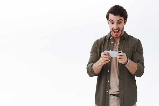 Opgewonden gelukkige man die prijs wint in het spel, online livestream van wedstrijd op mobiele telefoon kijkt