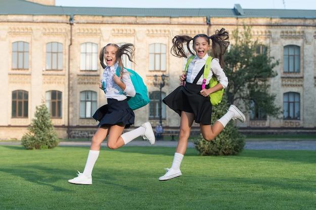 Opgewonden gelukkige meisjes schooluniform rennen, schiet op concept.