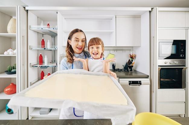 Opgewonden gelukkige moeder en dochter die bakplaat met vloeibaar cakedeeg erop hameren