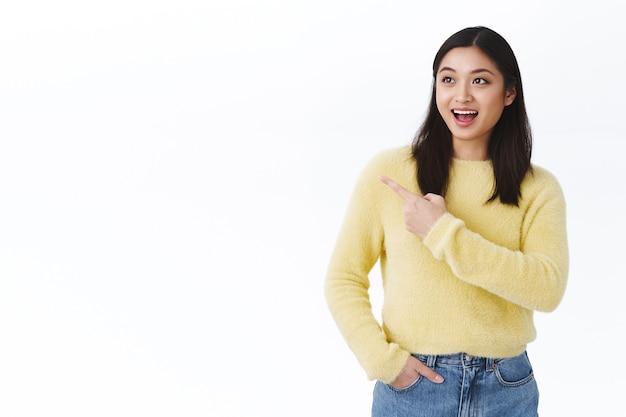 Opgewonden gelukkige mooie aziatische vrouwelijke student in gele trui, glimlachend en hijgend verbaasd, prachtig product ziend, geweldige promotie, wijzende vinger links naar lege witte kopieerruimte