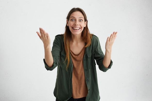 Opgewonden gelukkige vrouw die haar handen met opwinding opheft en haar triomf op de wedstrijd demonstreert. prachtig vrouwtje met brede glimlach tevreden met de overwinning