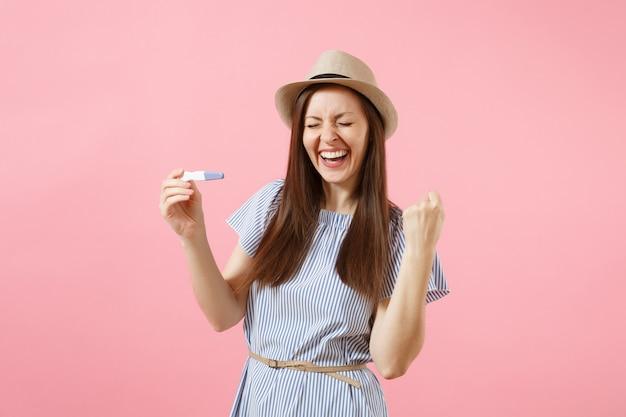 Opgewonden gelukkige vrouw in blauwe jurk, hoed in de hand houden, kijken naar zwangerschapstest geïsoleerd op roze achtergrond. medische gezondheidszorg gynaecologische, zwangerschap vruchtbaarheid moederschap mensen concept. ruimte kopiëren.