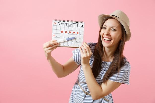 Opgewonden gelukkige vrouw in blauwe jurk, hoed in de hand houden zwangerschapstest, periodenkalender voor het controleren van menstruatiedagen geïsoleerd op roze achtergrond. medisch, gezondheidszorg, gynaecologisch concept. ruimte kopiëren.