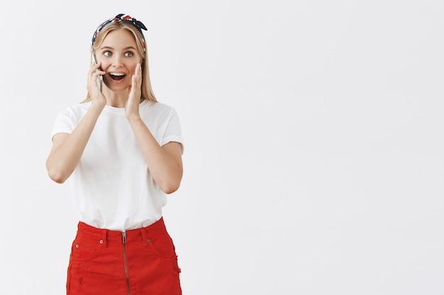 Opgewonden gelukkige vrouw praten aan de telefoon en verbaasd kijken