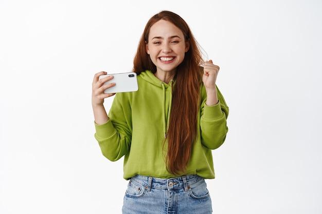 Opgewonden gembermeisje dat horizontale smartphone vasthoudt en wint, tevreden glimlacht, triomfeert van online prestatie, staande op wit
