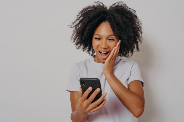 Opgewonden gemengd ras etniciteit millennial meisje geïsoleerd op witte studio achtergrond gevoel heerlijk winnen op mobiele telefoon app, dolblij gelukkige afrikaanse jonge vrouw krijgt geweldig nieuws op smartphone