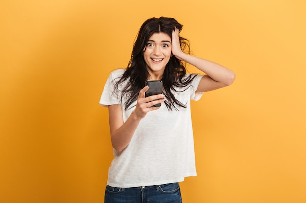 Opgewonden geschokt jonge mooie vrouw chatten via de mobiele telefoon.