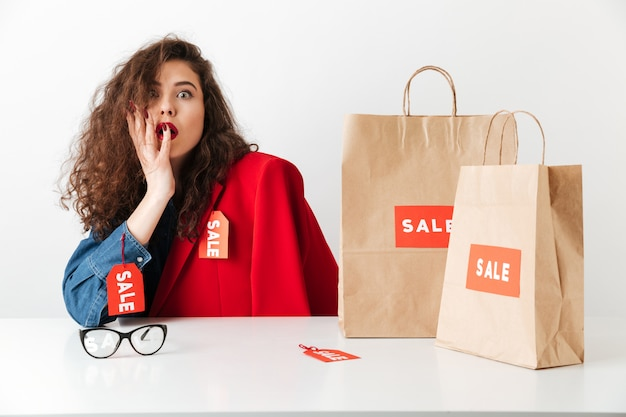 Opgewonden geschokt verkoop vrouw zitten met papieren boodschappentassen