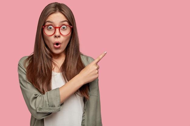 Opgewonden geschokte student poseert tegen de roze muur
