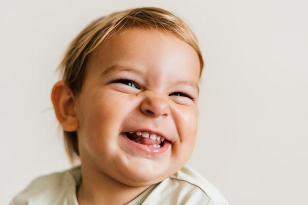 Opgewonden gezicht van een kleine baby peuter op witte achtergrond